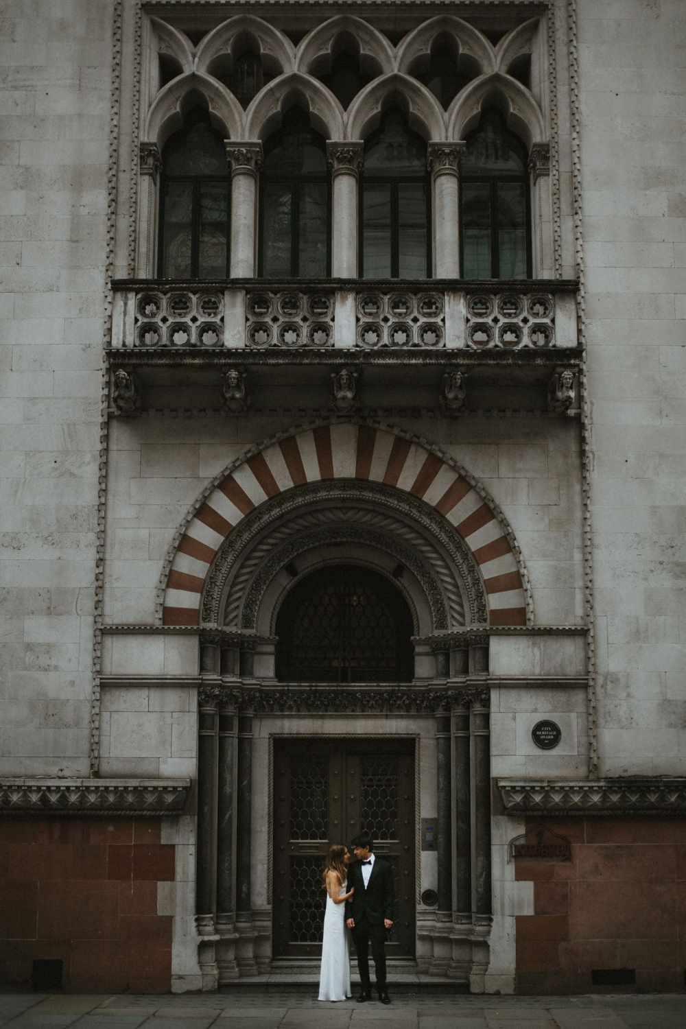 Bride and groom outside beautiful building for wedding portraits in London