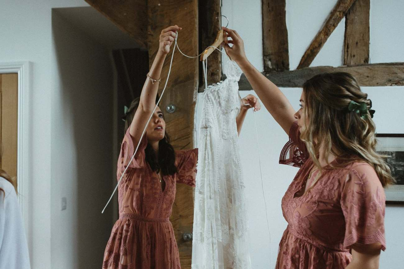 Bridesmaids holding up Rue De Seine wedding dress