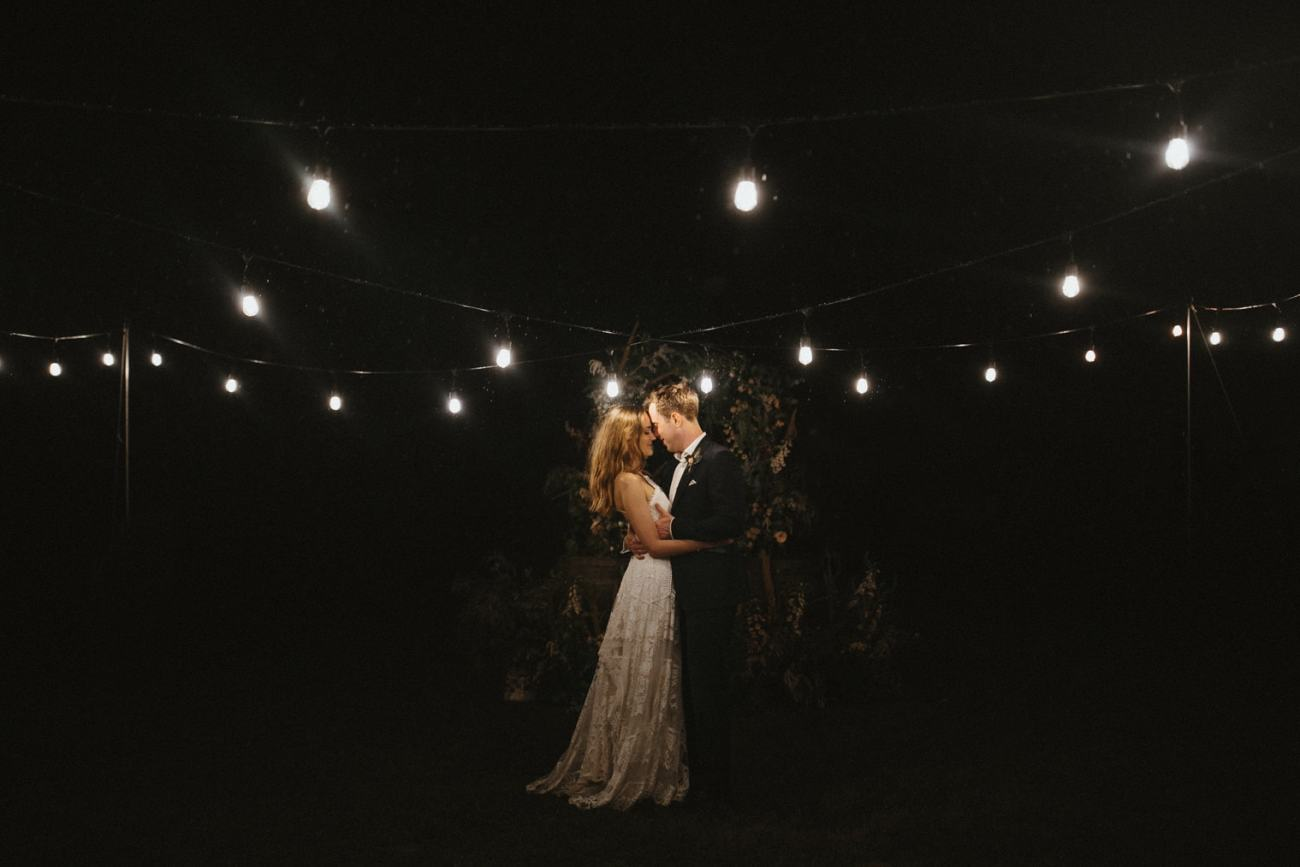 Bride and groom under festoon lighting during their outdoor wedding in essex