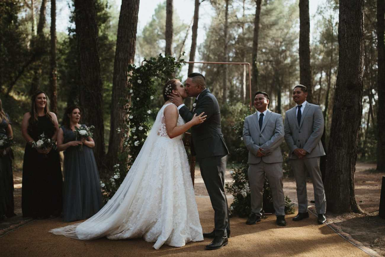 Bride and groom first kiss during outdoor forest ceremony in Spain
