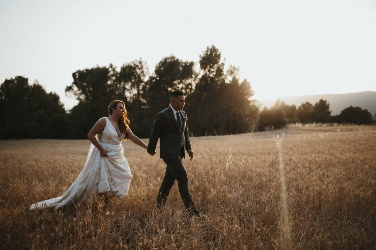 Bride and Groom walking through wheat field at sunset for portraits