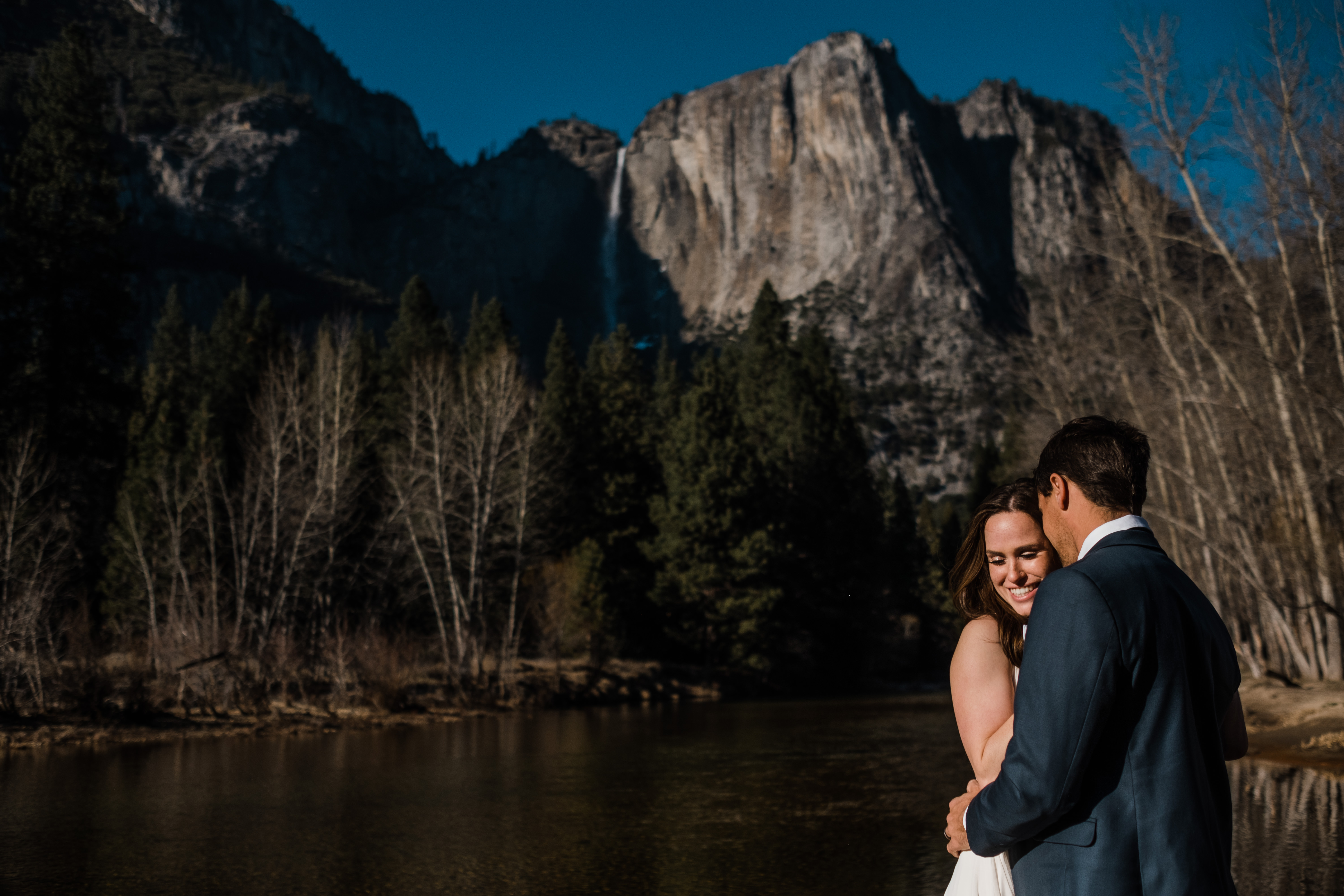 Ryan and Kim snuggle up in front of one of Yosemite's giant towering waterfalls during their adventure elopement session.