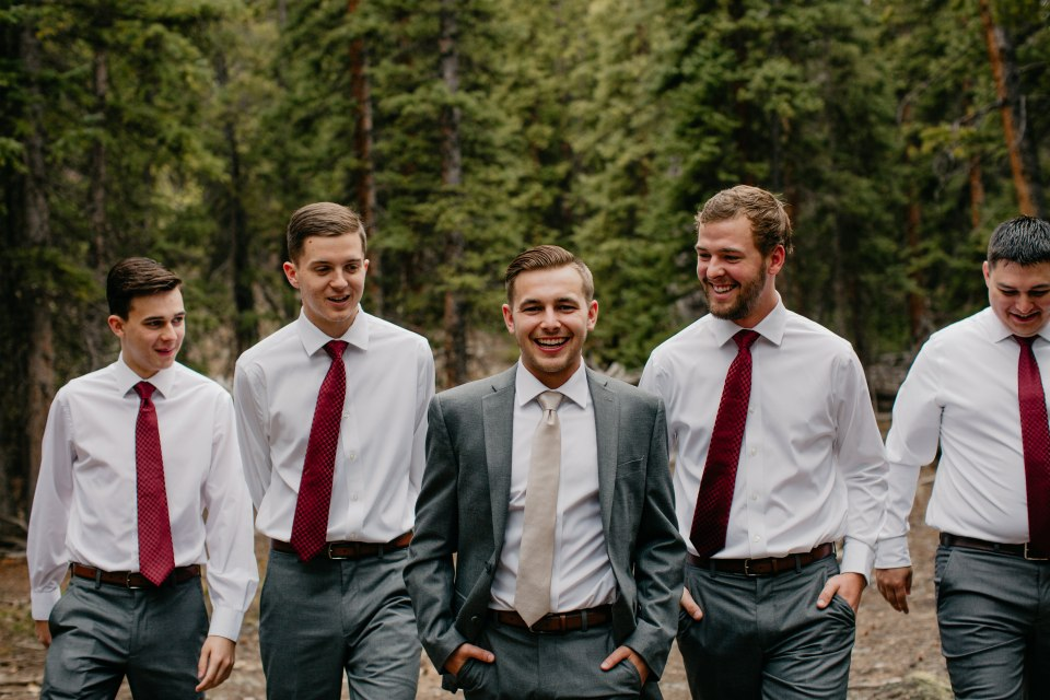 The groom and his groomsmen take a stroll through the evergreens.