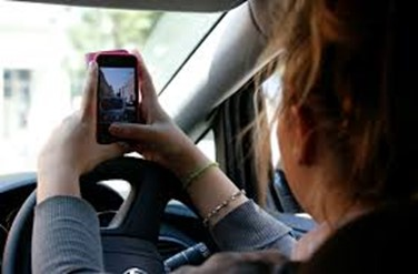 woman holding a mobile phone whilst driving