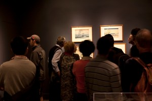 Visitors in dark gallery, looking at objects in pools of light.