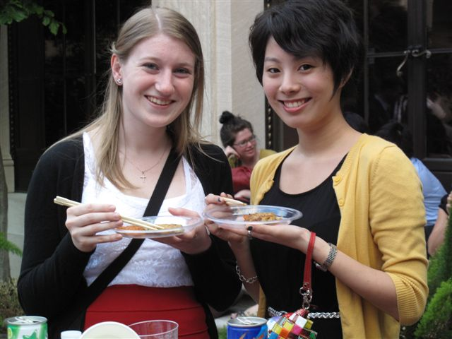 Two young women smiling with chopsticks and plates of kimchi.