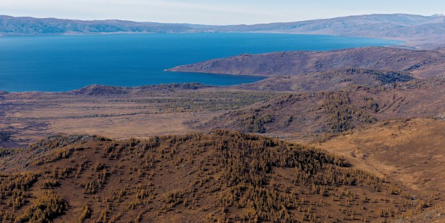 Brown green hills in foreground, blue lake in background.