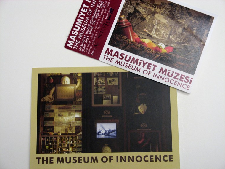 Burgundy ticket and gold postcard from the Museum of Innocence