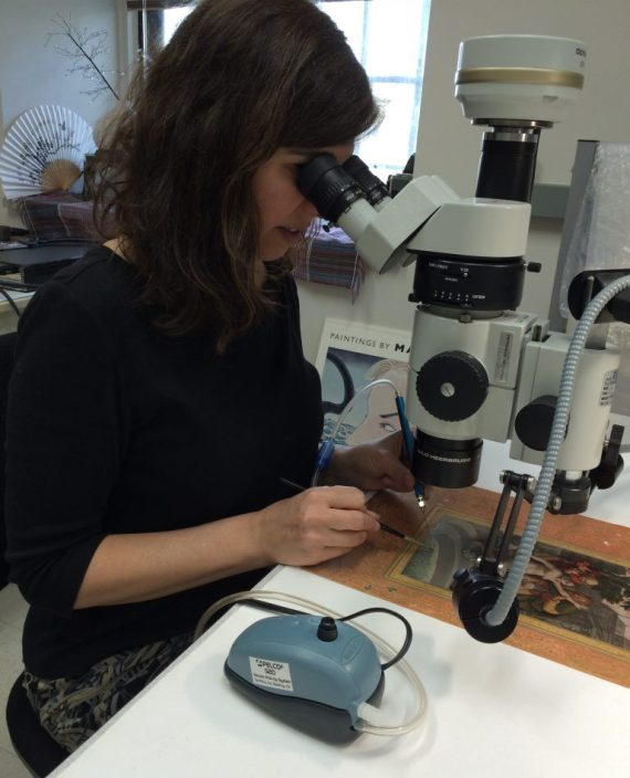 Emily Jacobson, paper conservsator at Freer|Sackler cleans a painting using a vacuum pick-up tool.