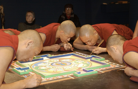 Tibetan monks working carefully to create the sand mandala in 2012.
