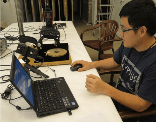 Xiao Ma, MCI intern, uses a portable Vis/NIR in to analyze a Neolithic jade bi.