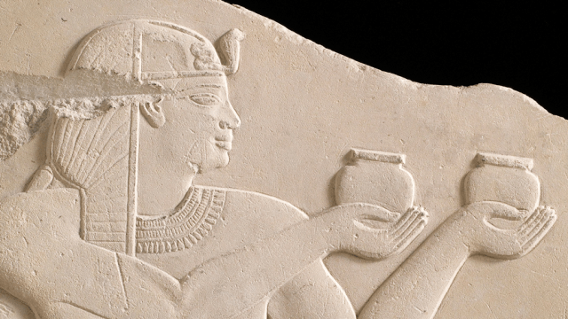 Detail of a stone relief of an Egyptian figure in flattened profile, holding a small jar up in either hand.