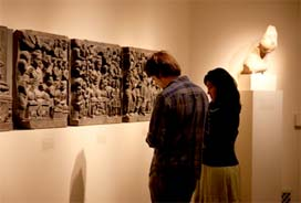 a man and a woman looking at a large stone relief