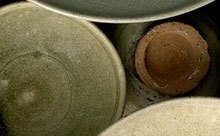 Overhead view of ceramic vessels of different sizes and colors arranged together.