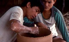 two men working on a clay vessel