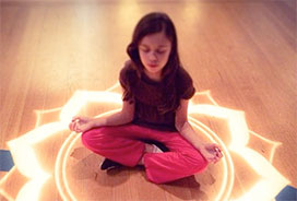 young girl meditating on a lotus flower that is projected onto the floor