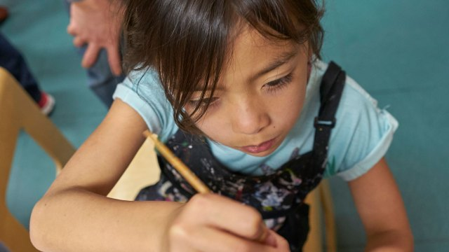 Young girl holding a pencil, writing, with a focused expression.