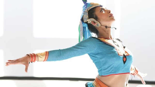 Dancer in traditional costume, posed with arms out to the side, looking gracefully up and to the right.