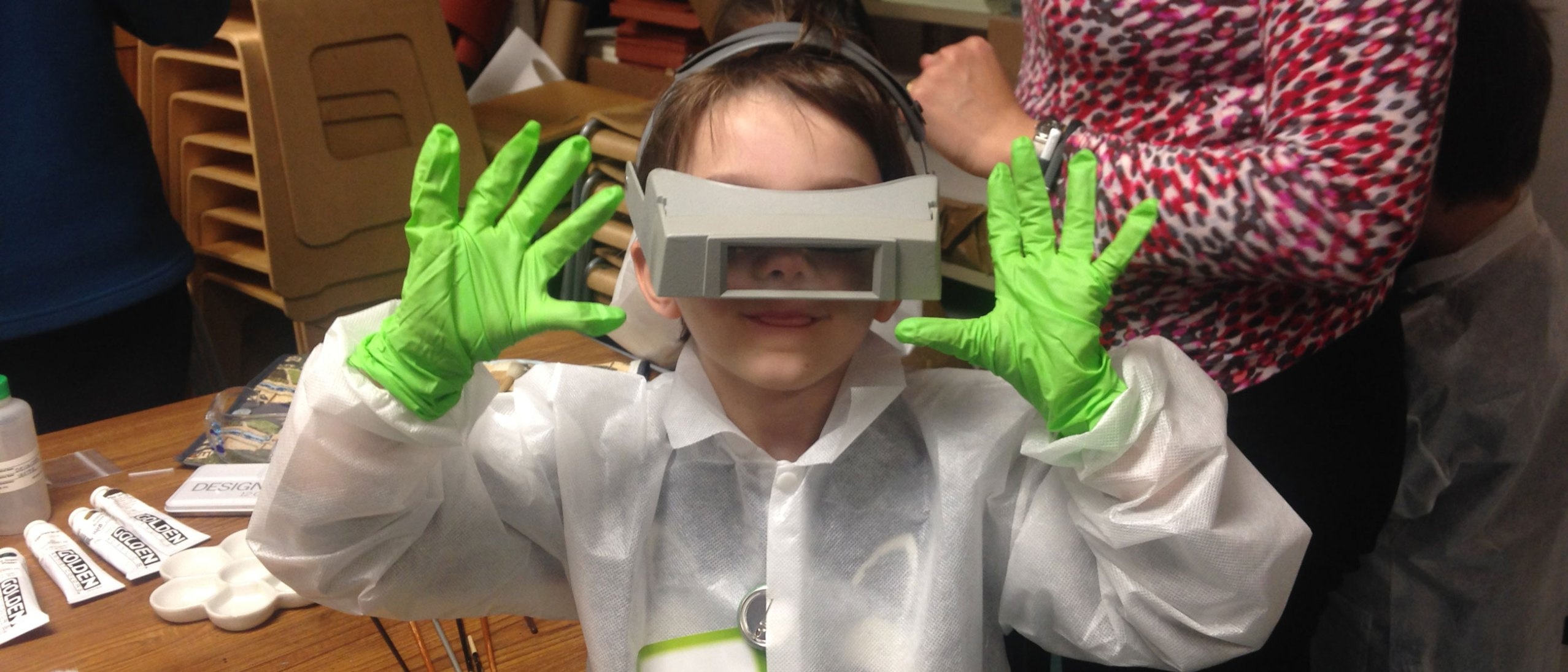 A boy shows off his gloves and safety goggles while attending the Art and Me Conservation workshop