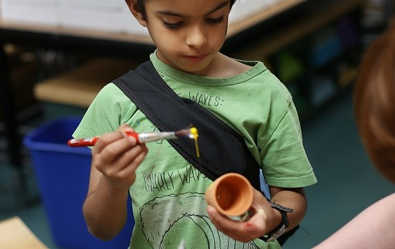 A young child in a green shirt with a green sleeping mask on his head. He is painting a small flower pot.