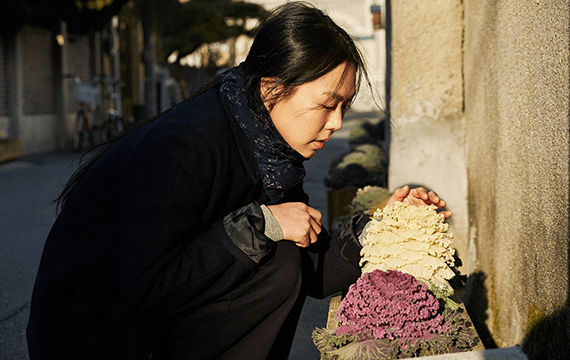 """Actress, Kim Min-hee, admiring white and purple plants in the film, """"On the Beach at Night Alone""""."""