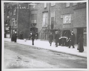 Black and White image of pallbearers from behind.