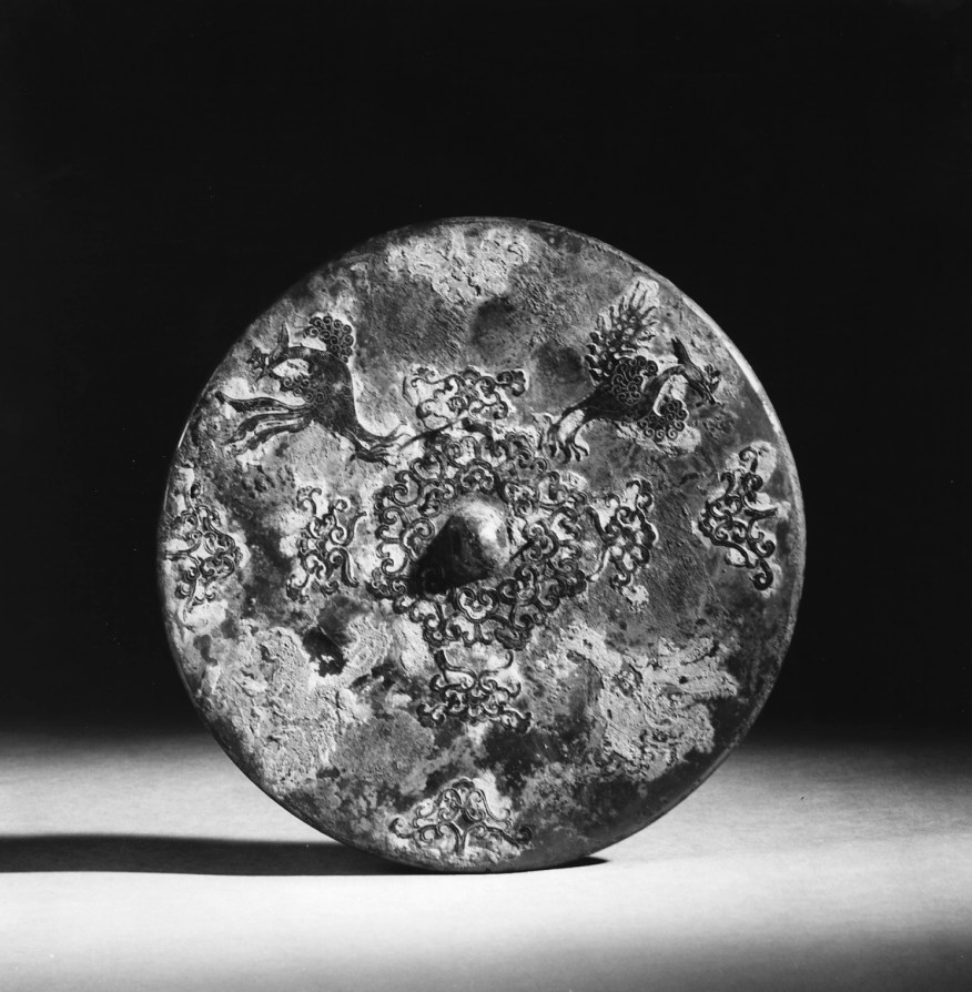 Photo of Bronze mirror with applied silver decoration. Tang dynasty, 7th century., Diam: 19 cm. (7 1/2 in.). Singer catalogue number: [1414].