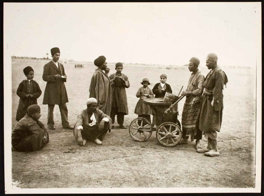 Black and white photo of men gathering around an ice cream vendor with a makeshift cart, against an open backdrop of dry dirt and sky.