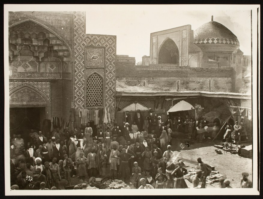Black and white photo of crowds outside a mosque.