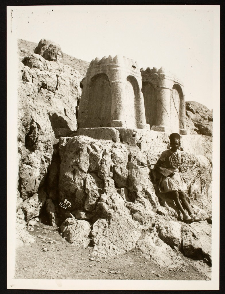 A figure leans against a cliff, on top of which is carved two fire altars.
