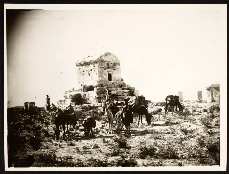 Two men look up at the mausoleum of Cyrus the Great while horses graze nearby.