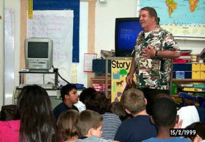 A Dr. Robert E. Brown speaks in front of children in an American classroom, dated 15/2/1999.