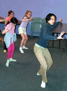 Kaori Okado teaches a group of girls a dance.