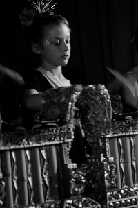 Black and white photo of a girl playing a gamelan gong.