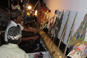 A puppeteer selects a wayang puppet from row of puppets lined up against a wall.