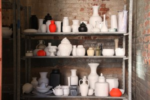 Three shelves full of ceramics, primed with white, black, and red bases
