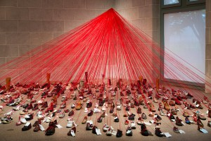 Hundreds of shoes with notes and red strings attached that all lead to a central locus
