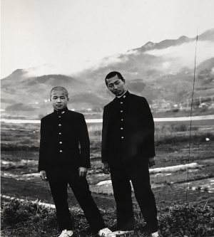 black and photo of two men in black uniforms