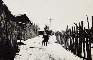 sepia-toned image of a person walking between two wooden fences next to a building
