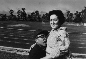 black and white photo of a man pressed to a smiling woman's bosom
