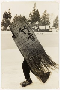 black white and sepia toned image of a man carrying a woven structure with japanese calligraphy