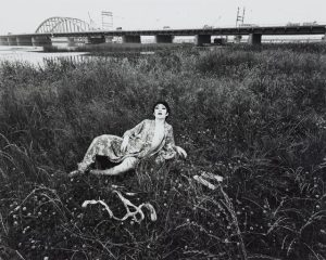 A black and white photo where the subject lounges in the grass