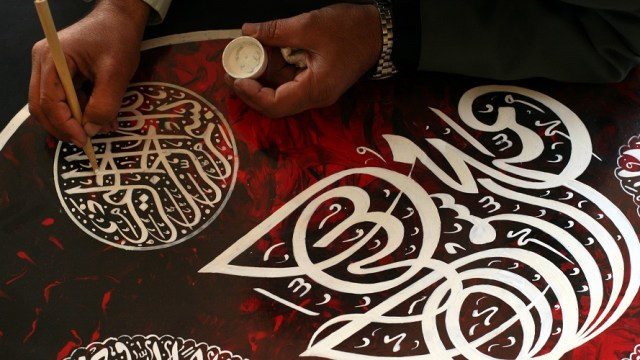 Calligrapher working in white ink on red
