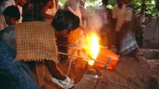 Metalworkers pouring a crucible of molten metal into the mold.