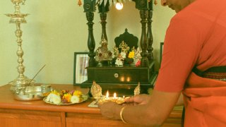 Woman lighting candles at a small, household shrine.