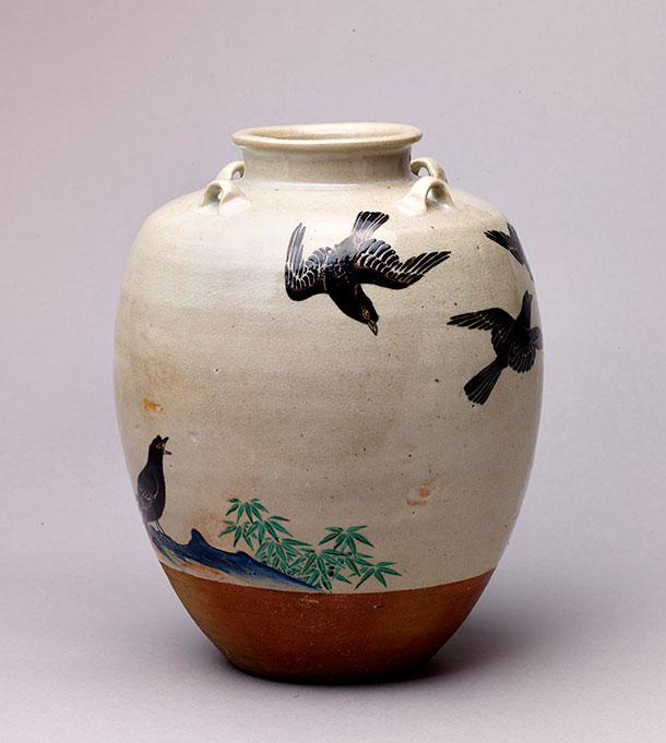 Jar decorated with black mynah birds against a white sky, above brown earth, blue mountains, and green foliage.