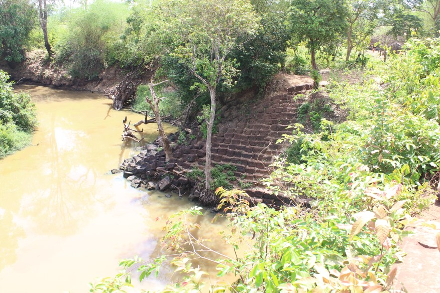 Stone stairs leading down to muddy river in the jungle