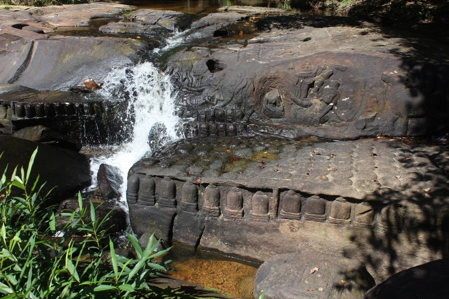 Rushing water over carvings of Vishnu and lingas in the partially dry riverbed