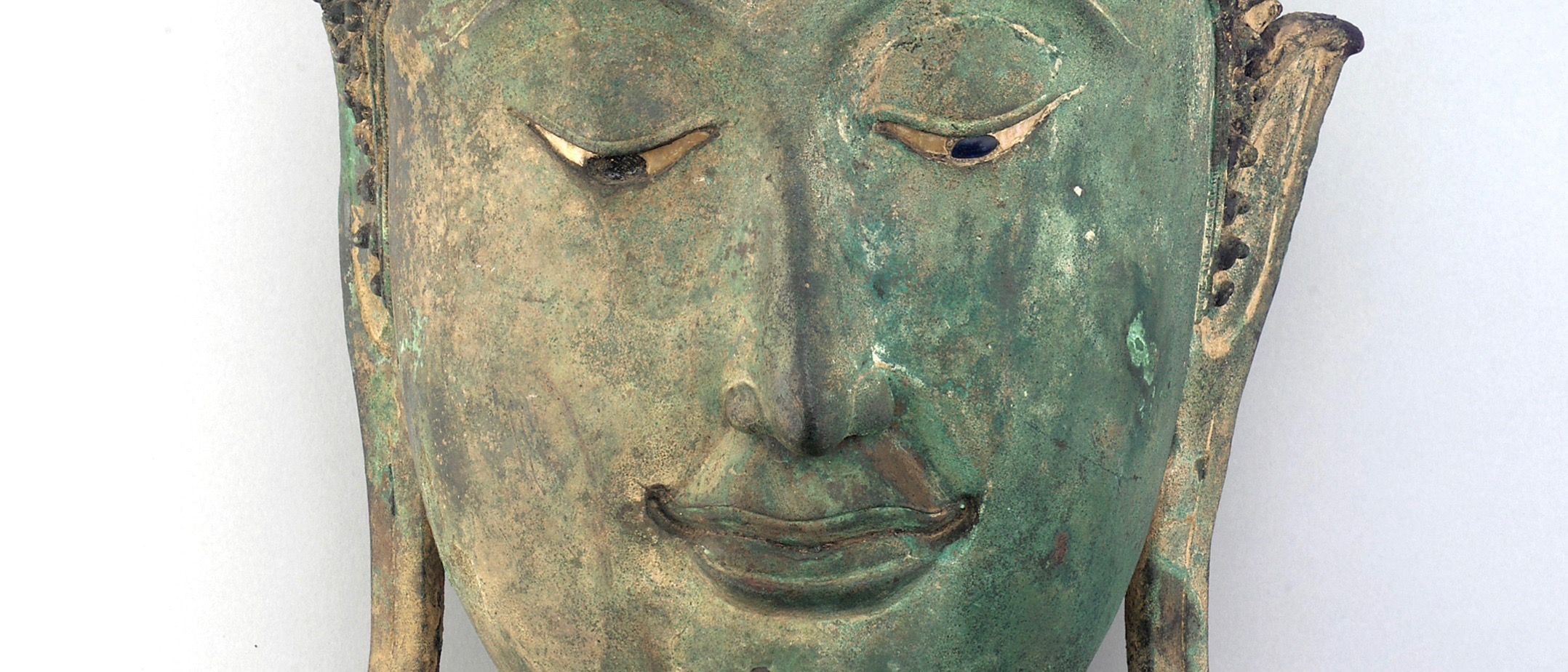 Sculpted head of a Buddha, made of bronze; its expression is plaintive, looking downward