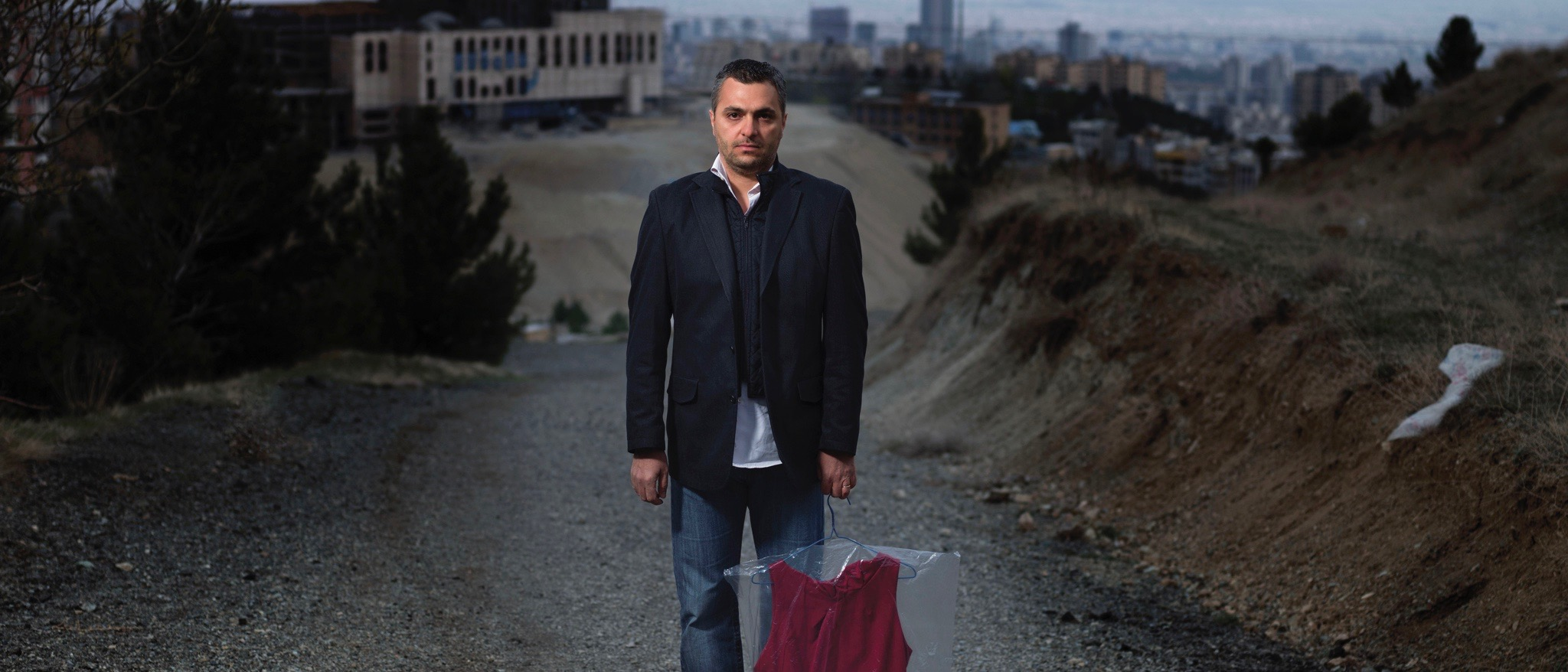 A man, standing in the middle of a gravel road, faces the viewer; in his left hand, he holds a crimson dress, wrapped in plastic, by its clothes hanger